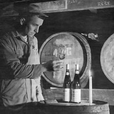 A black and white image of Richard Sommer looking at a glass of wine in the barrel room