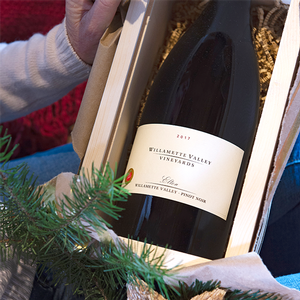 Women opens Collector's Dream package with Pinot Noir Magnum in a wood box
