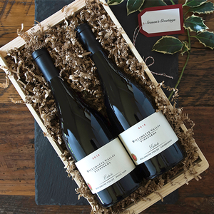 A bottle of Pinot Noir and Chardonnay in a wood box with holly