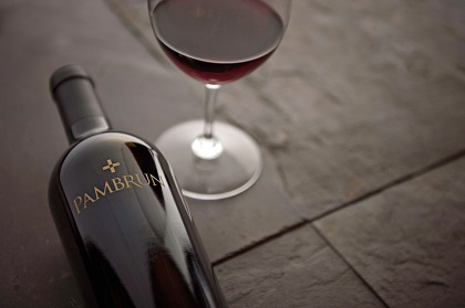 Bottle of Pambrun wine next to a glass of Merlot