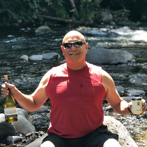 CFO Rich holding Pnot Gris next to the Breitenbush River while camping