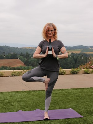 Suzanne doing yoga while holding a bottle of wine