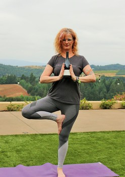 Winery Ambassador Suzanne Zupancic holding wine on yoga mat