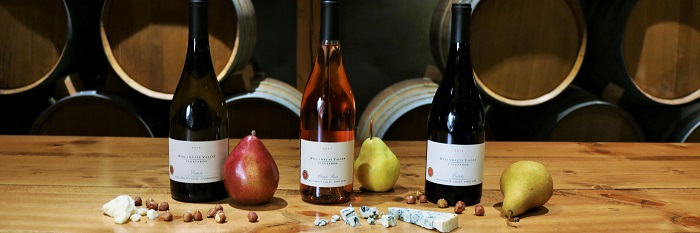 Three bottles of WVV wine with pears, cheese and hazelnuts on the table with barrels behind