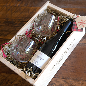 Bottle of Pinot Noir and two stemless win glasses inside a wooden box