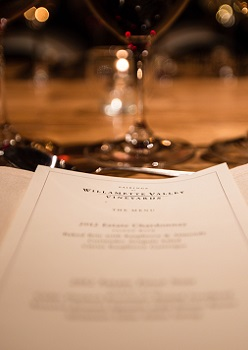 Dinner Menu placed on napkin with wine glasses behind it